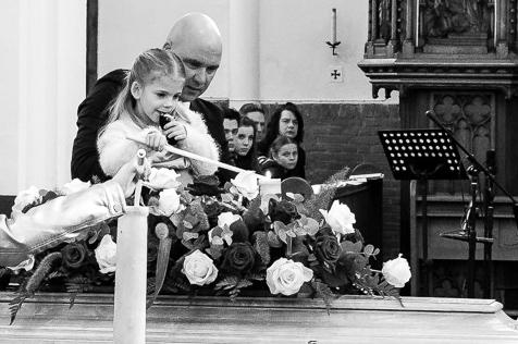 kinderen-steken-een-kaars-aan-tijdens-de-uitvaart-van-hun-vader